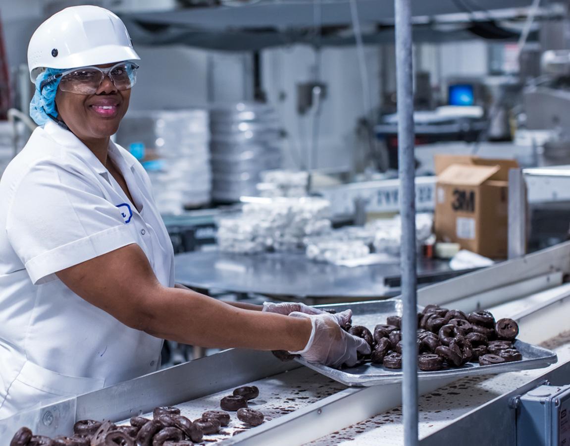 Entenmann's employee working near conveyor belt of donuts